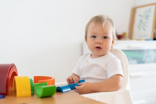 Blond ciekawskie dziecko bawiące się geometrycznymi drewnianymi figurami koncepcja edukacji dziecka w domu