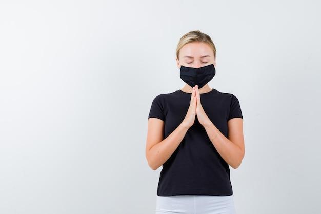 Blond dama ściskając ręce podczas modlitwy w czarnej koszulce na białym tle