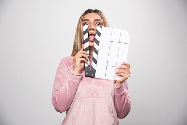 Blond dama w różowej bluzie trzyma pustą deskę do klapy i wkłada przez nią część swojego ciała.