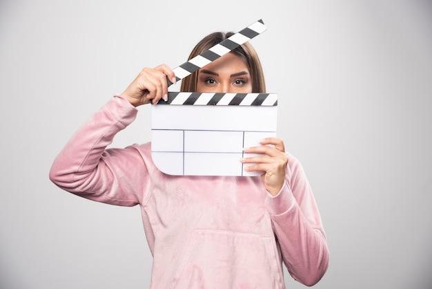 Blond dama w różowej bluzie trzyma pustą deskę klapy i przegląda ją.