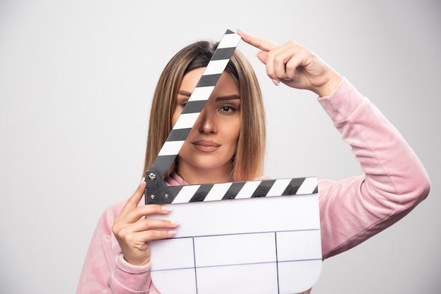 Blond dama w różowej bluzie trzyma pustą deskę klapy i przegląda ją