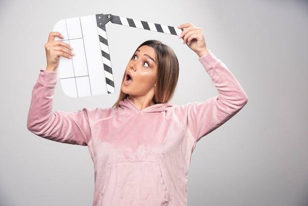Blond dama w różowej bluzie trzymająca pustą tablicę klapy wygląda na zaskoczoną i zdezorientowaną.