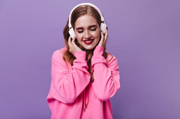 Blond dama w różowej bluzie uśmiecha się i słucha muzyki w słuchawkach