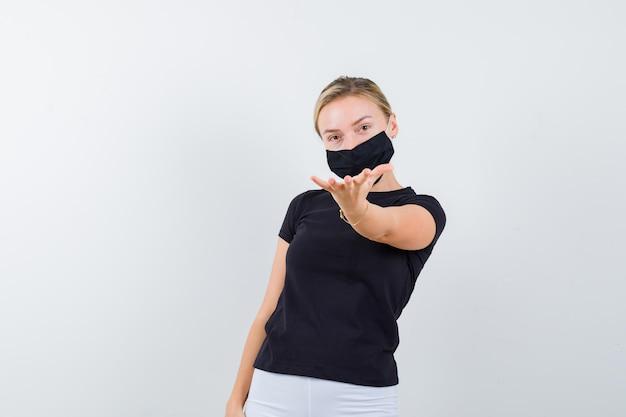 Blond dama wyciąga rękę w kierunku kamery w czarnej koszulce na białym tle