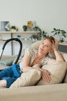 Blond dojrzała kobieta siedzi na kanapie w środowisku domowym, relaksując się po czyszczeniu podłogi w salonie z odkurzaczem