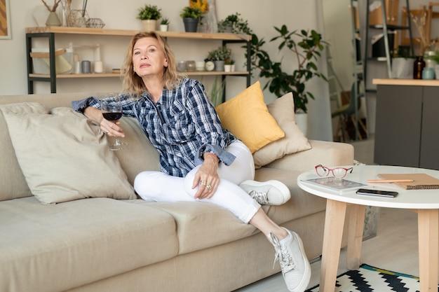 Blond dojrzała kobieta w casual, popijając kieliszek czerwonego wina, relaksując się na kanapie z poduszkami w salonie, podczas pobytu w domu