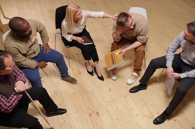 Blond dojrzała psycholog dotyka ramienia młodego brodatego mężczyzny, jednocześnie go pocieszając i udzielając porad dotyczących jego problemu