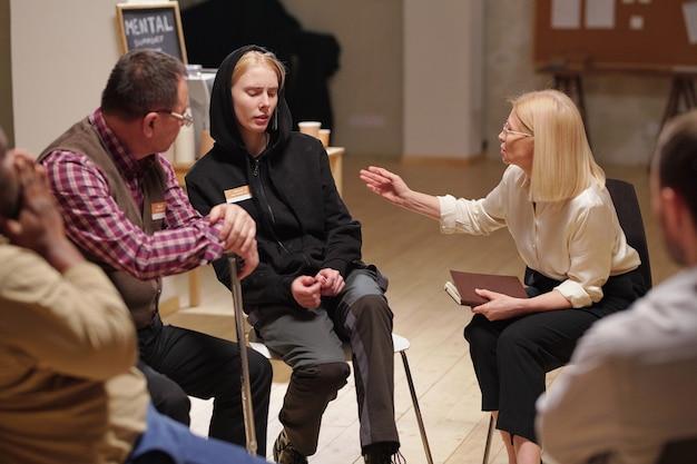 Blond doradczyni i dojrzały pacjent patrzący na zmartwioną i przerażoną dziewczynę siedzącą między nimi, podczas gdy psycholog próbuje ją pocieszyć