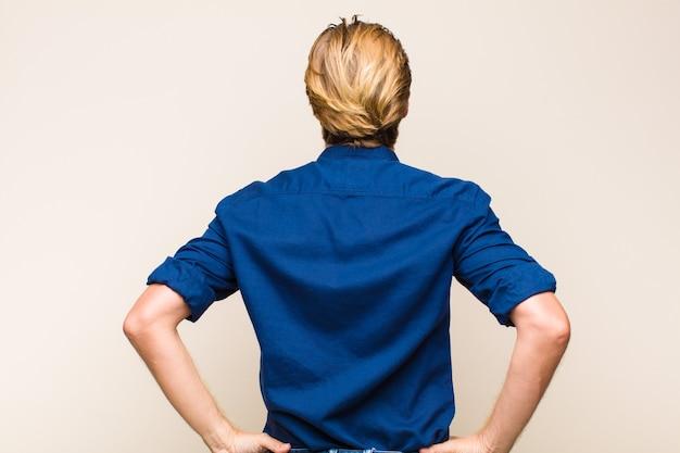 Blond dorosły kaukaski mężczyzna czuje się zdezorientowany lub pełny lub wątpliwości i pytania, zastanawiając się, z rękami na biodrach, widok z tyłu