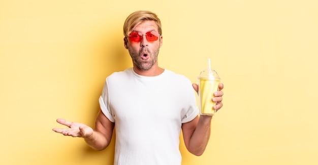 Blond dorosły mężczyzna czuje się bardzo zszokowany i zaskoczony koktajlem mlecznym