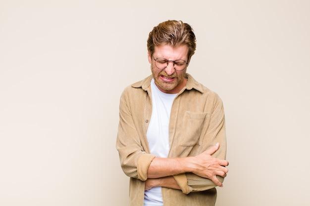 Blond dorosły mężczyzna czuje się niespokojny, chory, chory i nieszczęśliwy, cierpi na ból brzucha lub grypę