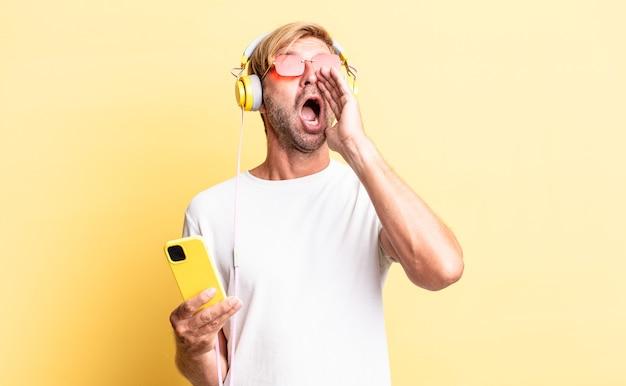 Blond dorosły mężczyzna czuje się szczęśliwy, wydając wielki okrzyk rękami przy ustach ze słuchawkami