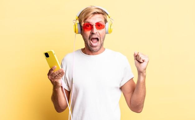 Blond dorosły mężczyzna czuje się zszokowany, śmieje się i świętuje sukces ze słuchawkami