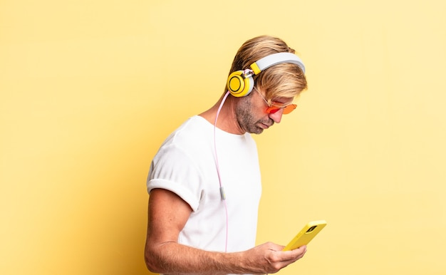 Blond dorosły mężczyzna myślący, wyobrażający sobie lub śniący na jawie ze słuchawkami w widoku profilu