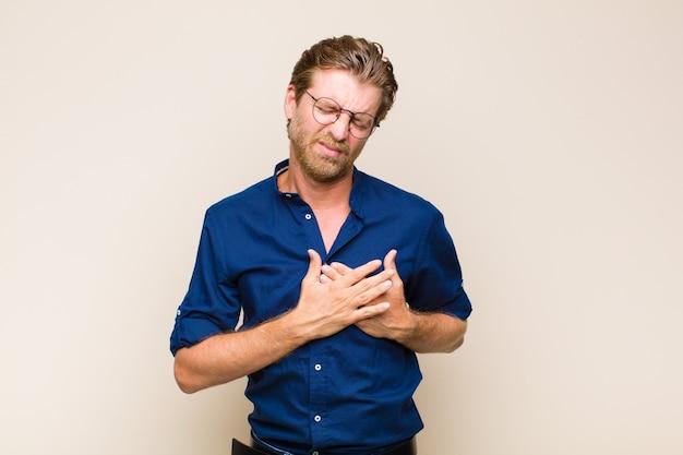 Blond dorosły mężczyzna rasy kaukaskiej wyglądający na smutnego, zranionego i złamanego serca, trzymający obie ręce blisko serca, płaczący i przygnębiony