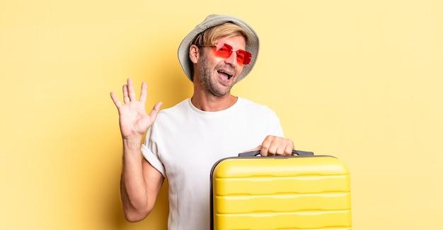 Blond dorosły mężczyzna uśmiecha się radośnie, machając ręką, witając cię i pozdrawiając. koncepcja podróżnika
