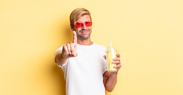 Blond dorosły mężczyzna uśmiechający się dumnie i pewnie robiąc numer jeden z koktajlem mlecznym