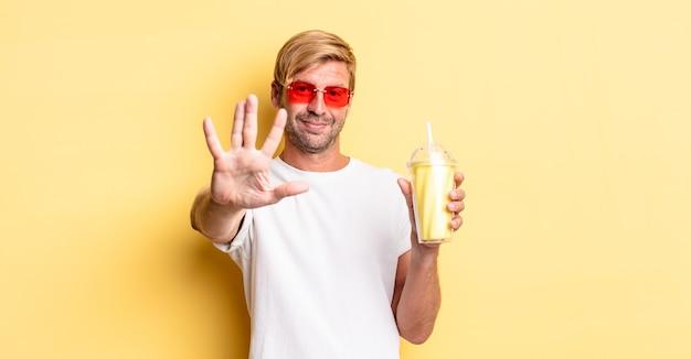 Blond dorosły mężczyzna uśmiechający się i wyglądający przyjaźnie, pokazujący numer pięć z koktajlem mlecznym