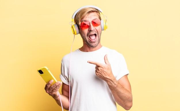 Blond dorosły mężczyzna wygląda na podekscytowanego i zaskoczonego, wskazując na bok ze słuchawkami