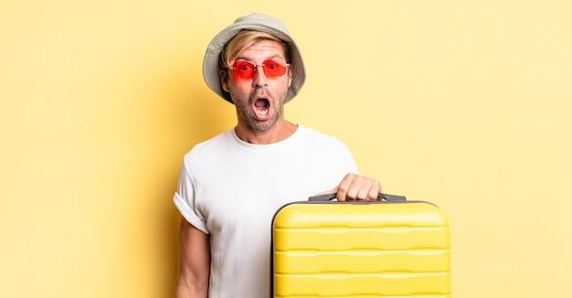 Blond dorosły mężczyzna wyglądający na bardzo zszokowanego lub zdziwionego. koncepcja podróżnika
