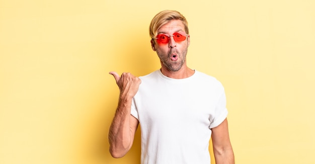 Blond dorosły mężczyzna wyglądający na zdziwionego z niedowierzaniem i noszący okulary przeciwsłoneczne
