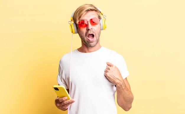 Blond dorosły mężczyzna wyglądający na zszokowanego i zaskoczonego z szeroko otwartymi ustami, wskazujący na siebie przez słuchawki