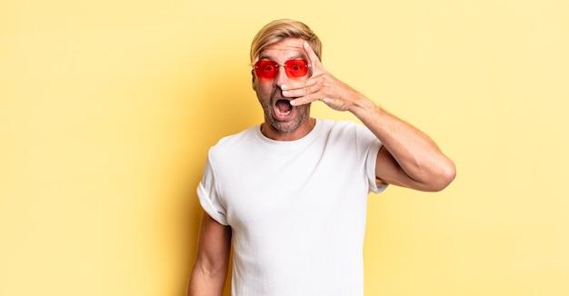 Blond dorosły mężczyzna wyglądający na zszokowanego, przestraszonego lub przerażonego, zakrywający twarz dłonią i noszący okulary przeciwsłoneczne