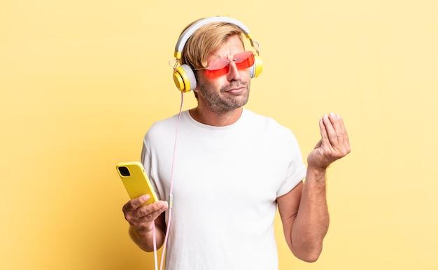 Blond dorosły mężczyzna wykonujący gest kaprysu lub pieniędzy, mówiący ci, aby zapłacić słuchawkami