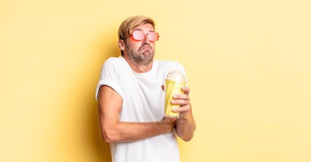 Blond dorosły mężczyzna wzrusza ramionami, czuje się zdezorientowany i niepewny przy koktajlu mlecznym