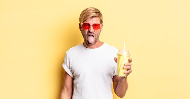 Blond dorosły mężczyzna z pogodnym i buntowniczym nastawieniem, żartuje i wystawia język z koktajlem mlecznym
