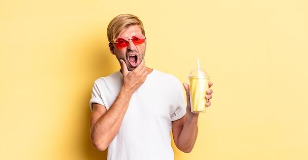 Blond dorosły mężczyzna z szeroko otwartymi ustami i oczami i ręką na brodzie z koktajlem mlecznym