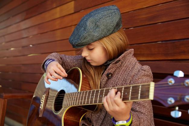 Blond dziecko dziewczynka gra na gitarze z beret zimowy