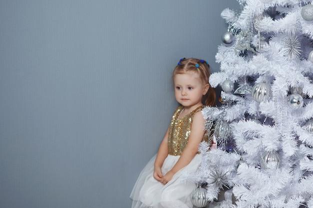 Blond dziecko z choinką. luksusowa dekoracja świąteczna.