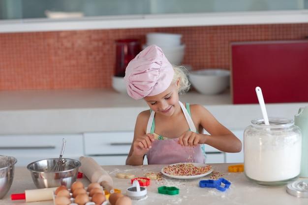 Blond dziewczyna pieczenia herbatniki dla jej rodziny