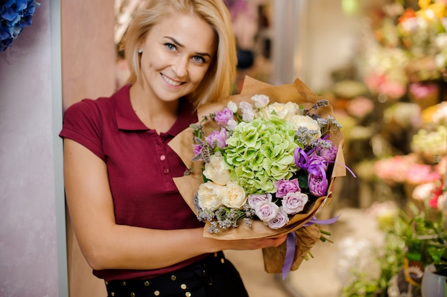 Blond dziewczyna uśmiecha się i trzyma w rękach stylowy bukiet róż, hortensji i piwonii