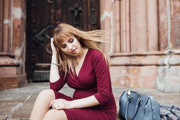 Blond dziewczyna w ciąży w bordowej sukience. w wielkim mieście. długie włosy. 9 miesięcy oczekiwania. szczęście być matką.