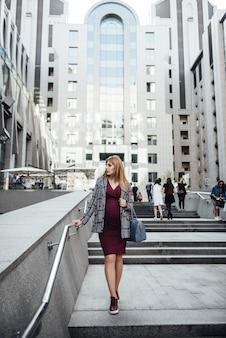 Blond dziewczyna w ciąży w bordowej sukience. w wielkim mieście. szkodliwy dla środowiska. długie włosy. 9 miesięcy w oczekiwaniu. wysokie budynki. tłum. podrażnienie. szczęście być mamą. tłum i irytacja.