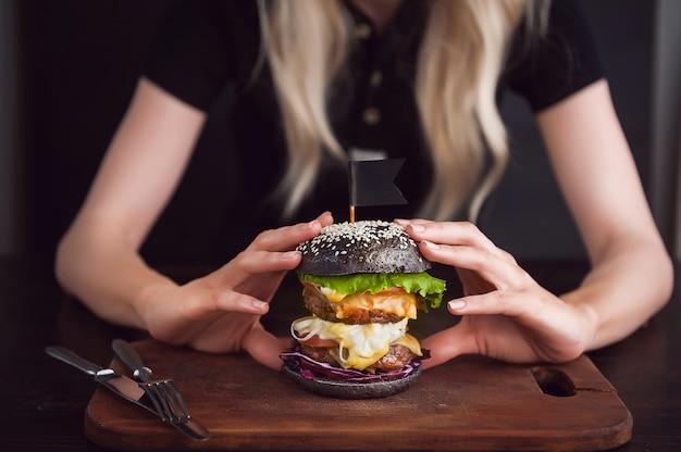 Blond dziewczyna w czarnej koszulce z wielkim czarnym burgerem w dłoniach