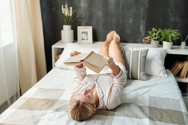 Blond dziewczyna w piżamie, leżąc na łóżku i czytając książkę przygotowując się do egzaminu lub dla przyjemności