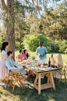 Blond dziewczyna z długimi włosami robi zdjęcie młodego afrykańskiego mężczyzny stojącego przed nią przy stole serwowanym z przyjaciółmi dookoła