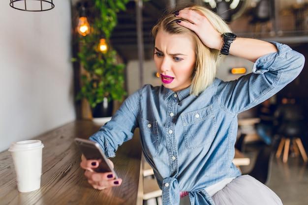 Blond dziewczyna z jasnoróżowymi ustami siedzi w kawiarni, picia kawy i patrząc na swojego smartfona. wygląda na zaskoczoną i bawi się włosami. nosi niebieską dżinsową koszulę
