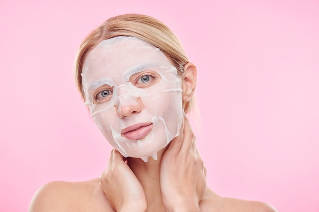Blond dziewczyna z tekstylną maską nawilżającą na twarzy, patrząc na ciebie, trzymając ręce na szyi w izolacji