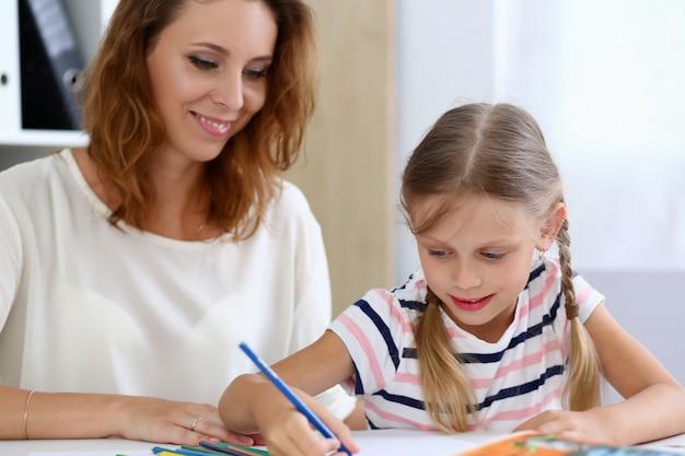 Blond dziewczynka trzymać w ręku ołówek rysunek coś