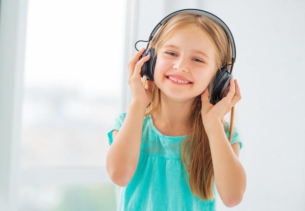 Blond dziewczynka uśmiecha się i słucha muzyki na słuchawkach