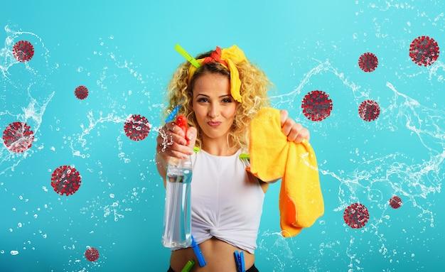 Blond gospodyni domowa rozpryskuje środek dezynfekujący, aby usunąć wirusy i bakterie covid-19. niebieskie tło