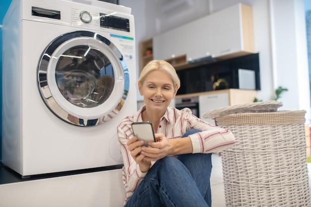 Blond gospodyni domowa w pasiastej koszuli siedzi w pobliżu pralki i trzyma smartfon