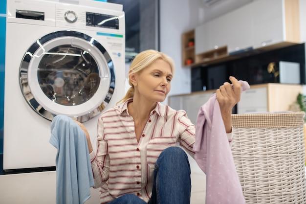 Blond gospodyni domowa w pasiastej koszuli siedzi w pobliżu pralki z dużą ilością ubrań