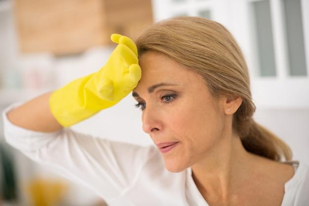 Blond gospodyni domowa w rękawiczkach ochronnych źle się czuje