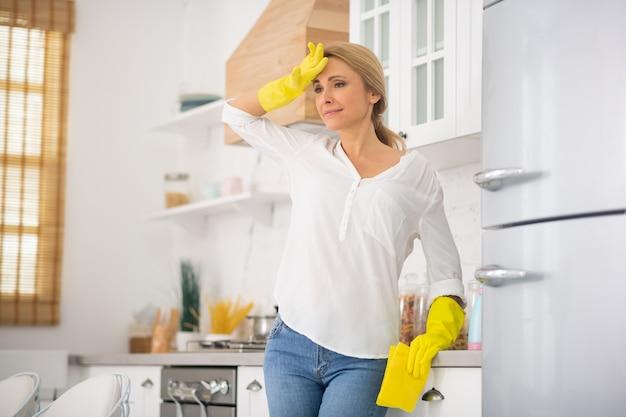 Blond gospodyni w rękawiczkach ochronnych źle się czuje