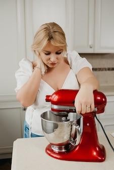 Ð blond gospodyni wpatruje się, wspierając się na czerwonym mikserze stojącym, podczas ubijania składników w kuchni. dziewczyna przygotowuje się do ugotowania pysznej cytrynowej tarty bezowej.
